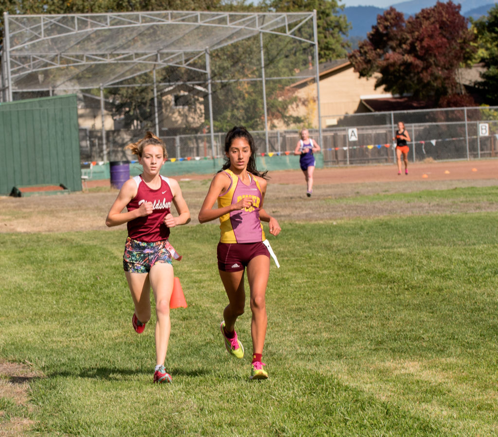 About Mid race and before the final Hill, Gabby and Cynthia are still stride for stride, with Amelia Wirt still in 3rd but Arcata's Soph. Riley Martel-Phillips is gaining ground